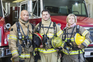 Portrait of a diverse group of three firefighters at the station standing in front of fire trucks with their protective gear. They are wearing tan suits with yellow reflective stripes, holding helmets and protective gloves.